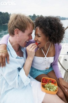 Man feeding a woman strawberries on a boat